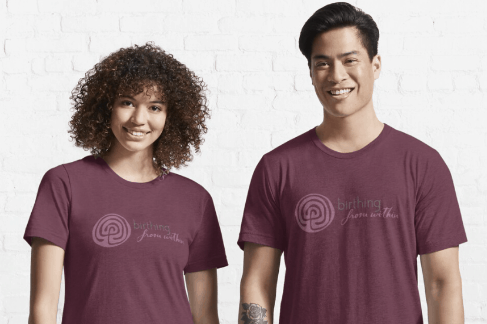 A Woman and Man both wear burgundy Birthing From Within T-shirts