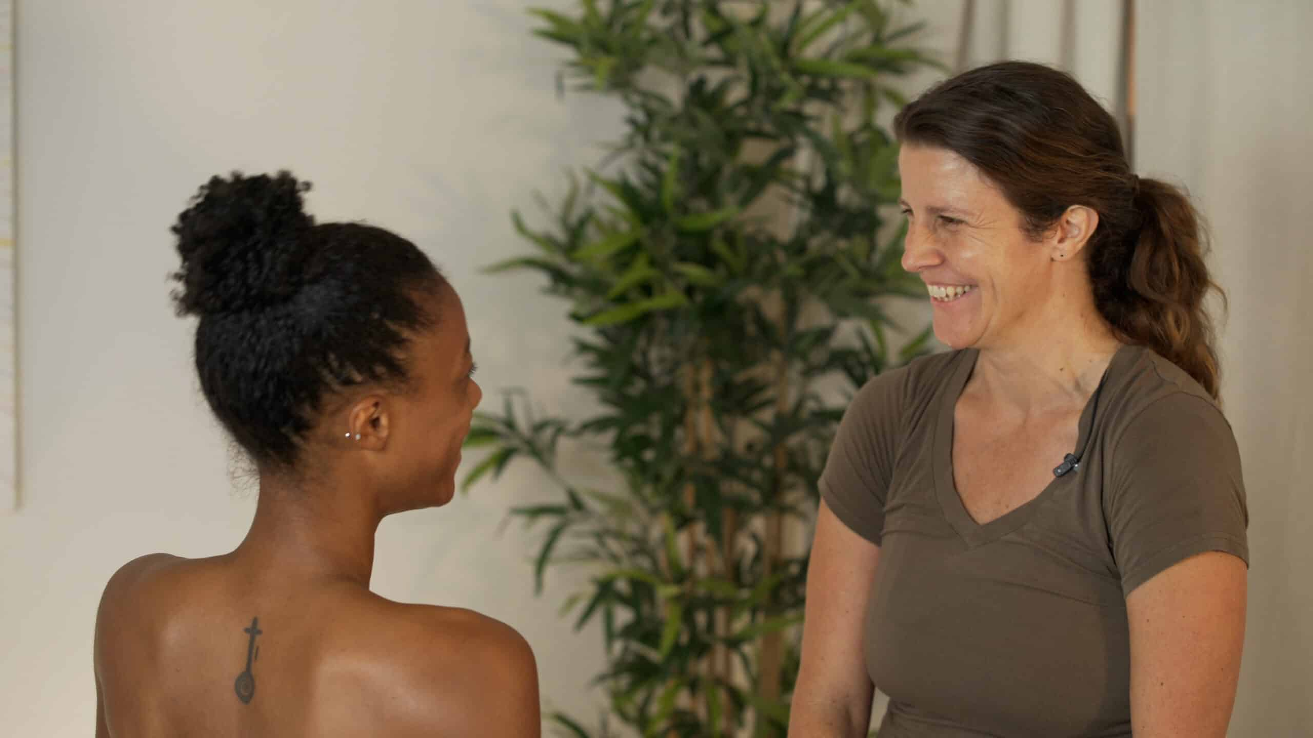 a massage therapist talks with a prenatal massage client