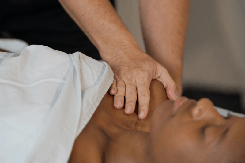 a pregnant person has their shoulder massaged by a massage therapist