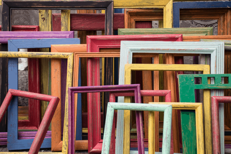 a photo full of wooden frames stacked against esch other in many different colors